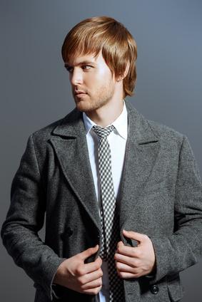 Portrait of a handsome man in an elegant coat. Beauty, fashion. Studio shot.
