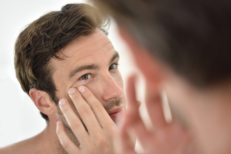 50065599 - handsome man applying facial cream in front of mirror