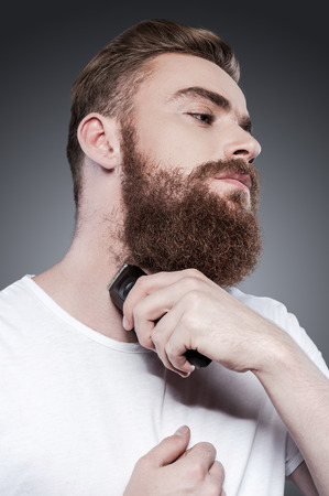 32264174 - making beard perfect. confident young bearded man shaving with electric razor while standing against grey background