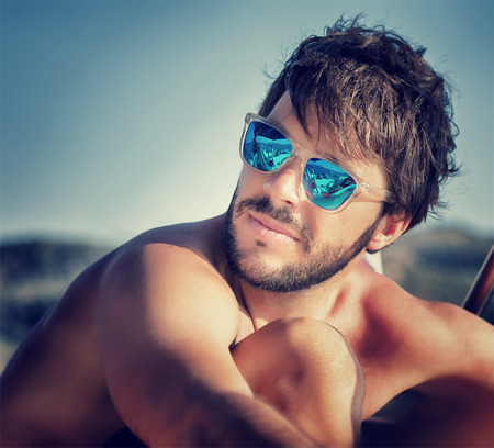 38609159 - closeup portrait of handsome man on the beach in mild sunset light, wearing blue stylish sunglasses, summer vacation concept