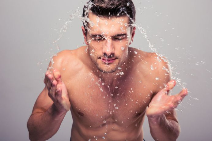 40945664 - young man spraying water on his face over gray background