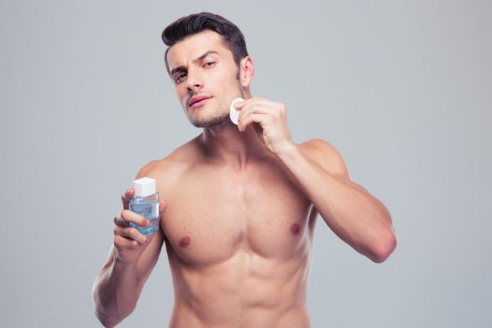 41047937 - man applying lotion after shave on face over gray background