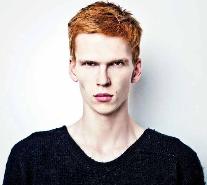 15576395 - young red haired man on light background