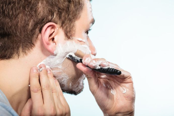 41446000 - health beauty and skin care concept. closeup young bearded man with foam on face shaving with razor on blue background.