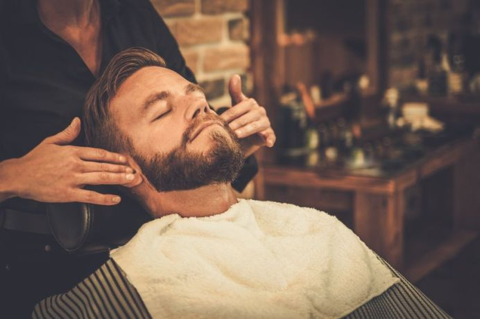 42273599 - hairstylist applying after shaving lotion in barber shop