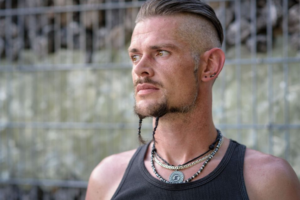 44171226 - tough guy with sparrow beard, undercut and black rip shirt standing thoughtful in front of a wall of stones