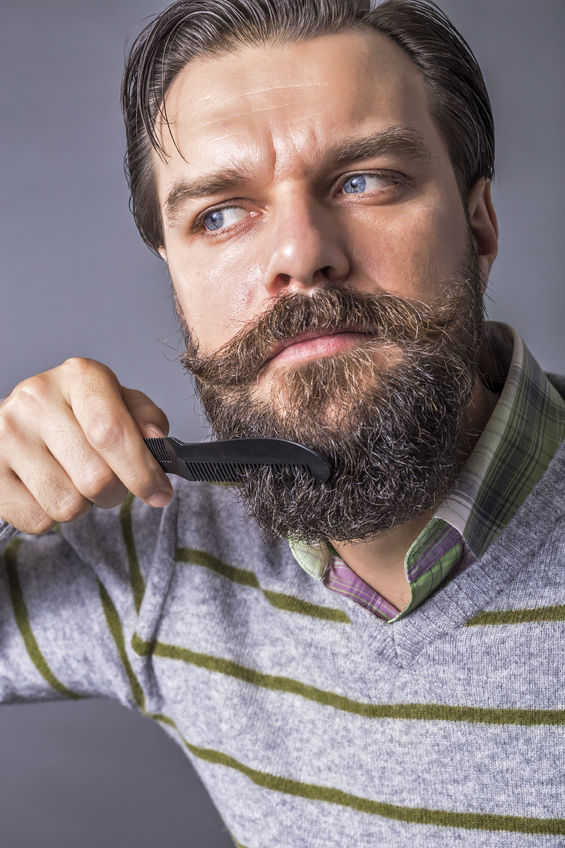 47497660 - closeup of young man brushing his beard over gray background