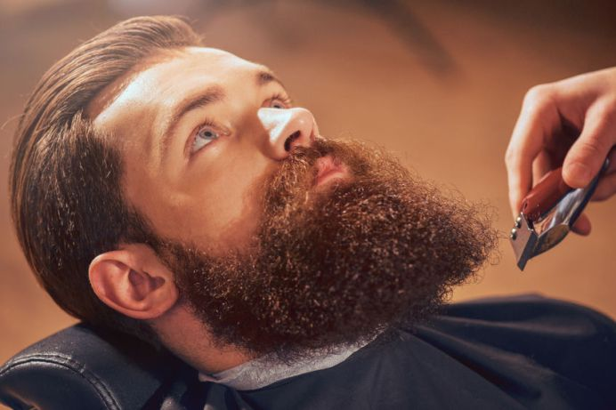 54552068 - ready for changes. pleasant handsome barbed man sitting in the barbershop while professional barber going to cut his beard