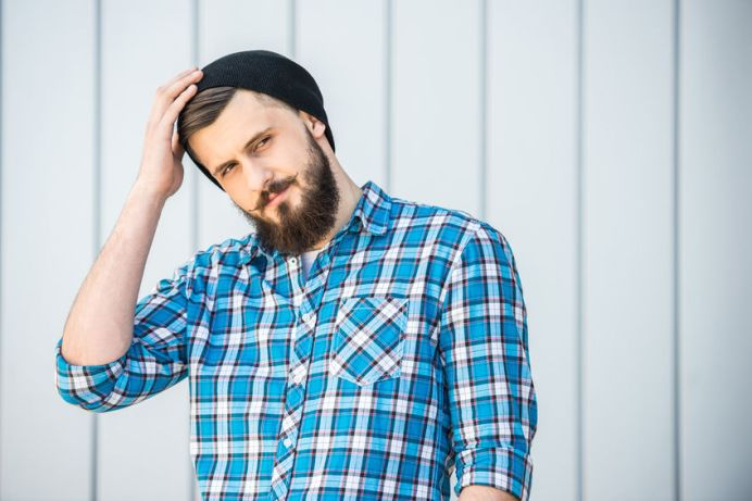 39393207 - portrait of young bearded man in hat is looking away. outdoor.