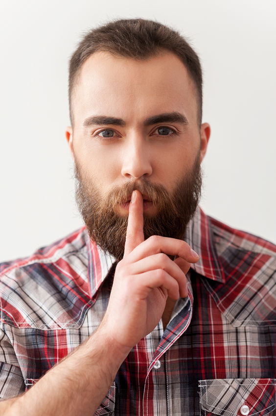 26366257 - keep silence. portrait of handsome young bearded man making salience sign
