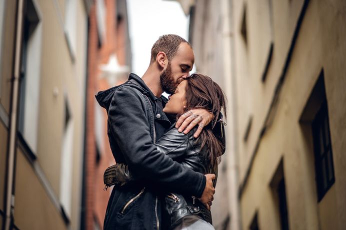 65175772 - positive bearded male kissing cute brunette female on a street in an old town.