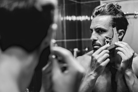 63276233 - hipster man shaving his beard in the bathroom